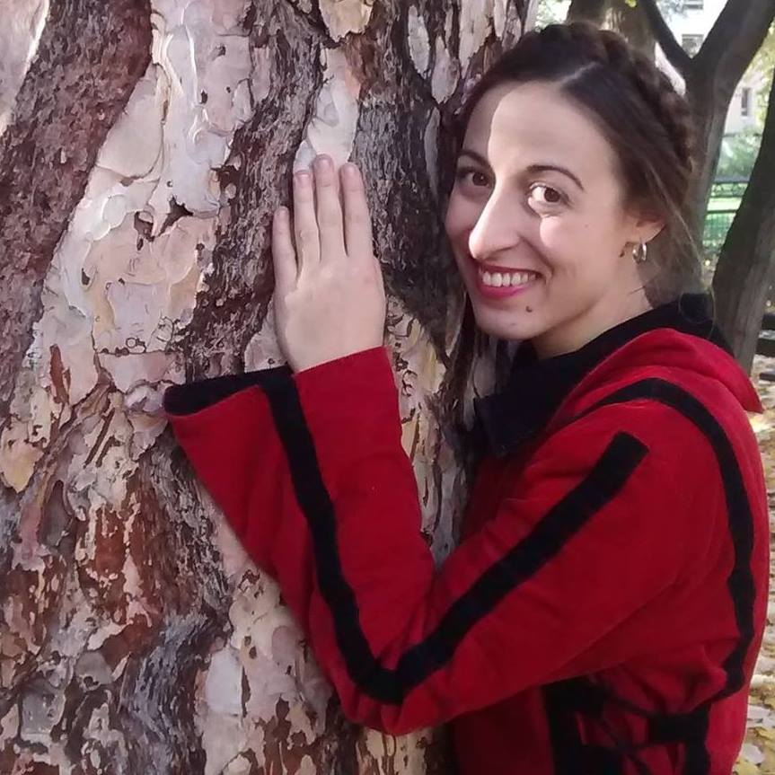 woman with a red jacket touching a tree