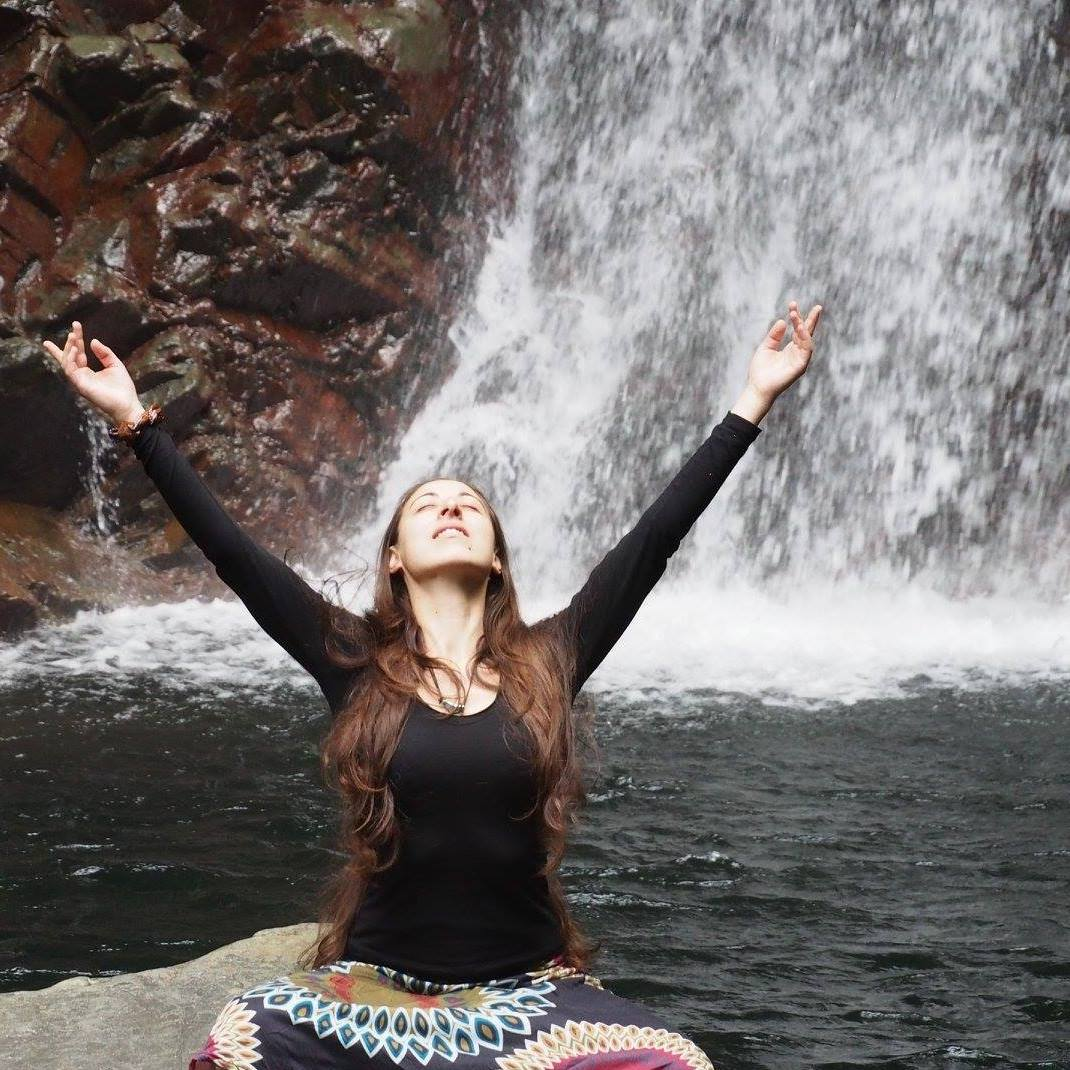 Woman meditating in front of a waterfall